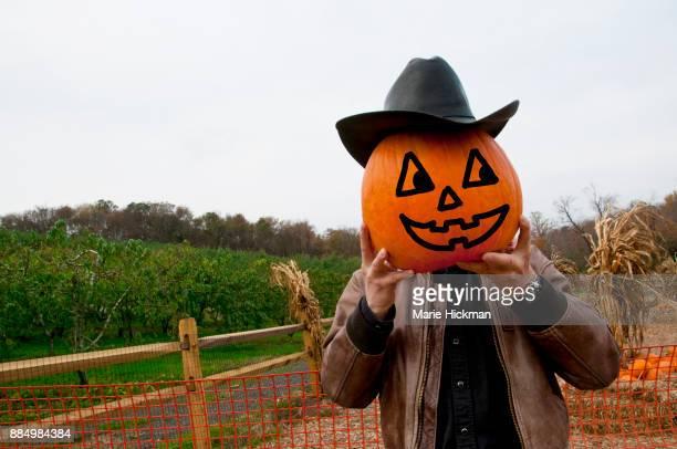 Man holding up a Jack O'Lantern pumpkin as his face.