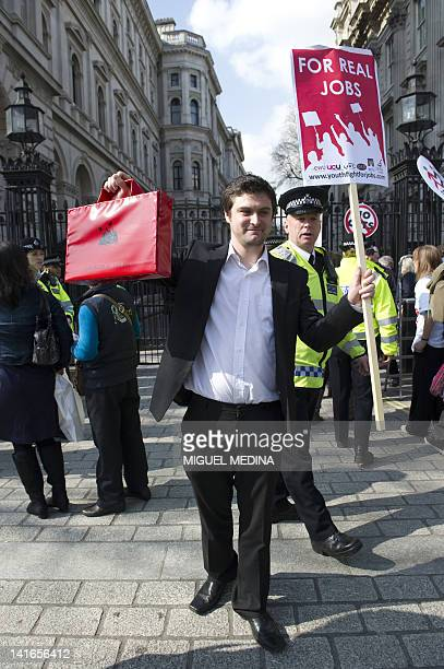 A man holding up a mockup of the Budget Box demonstrates in front of Downing street against the budget in central London on March 21 2012 The British...
