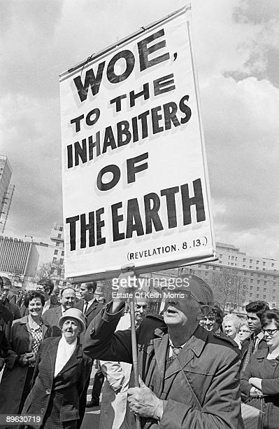 A man holding up a placard bearing an ominous biblical quote from the Book of Revelation London 1968