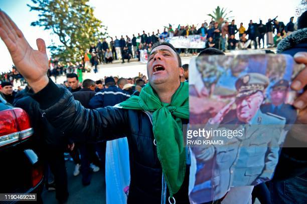 A man holding up a portrait of Algeria's late military chief Lieutenant general Ahmed Gaid Salah chants slogans as people gather outside the Palais...