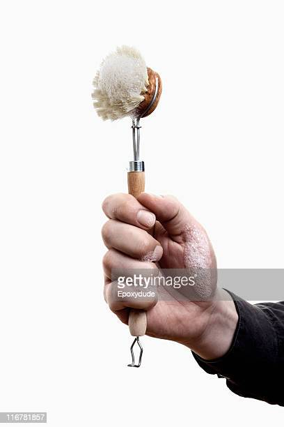 A man holding up a scrub brush with soap suds on it, close-up of hand