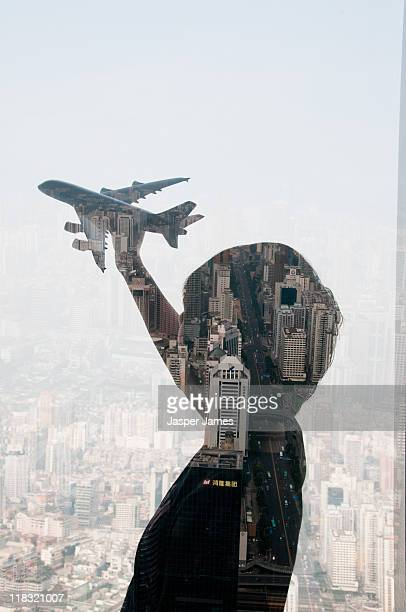man holding up airplane with cityscape,double expo