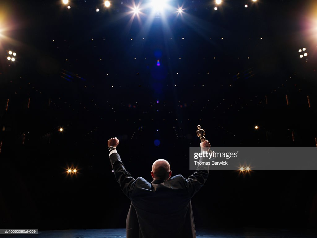 Man holding up award towards audience, rear view : Foto stock