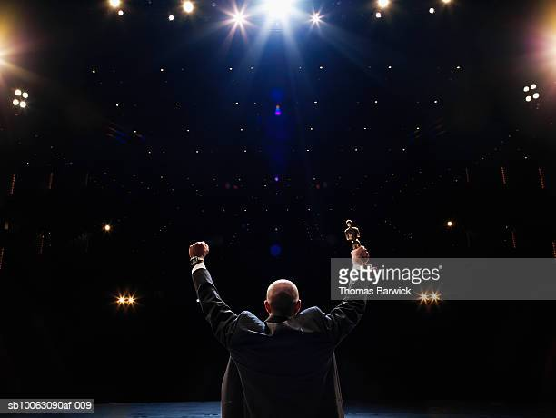 man holding up award towards audience, rear view - award stockfoto's en -beelden