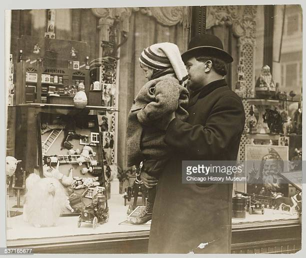 Man holding up child to look at Christmas toys and decorations in a store window circa 1910