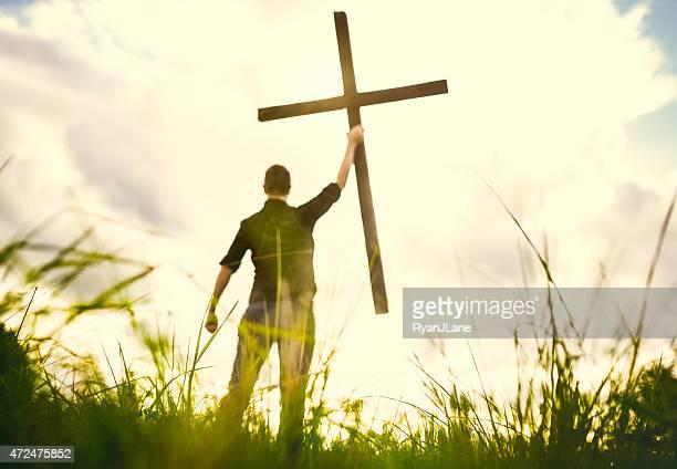 Homme tenant une croix du Christ