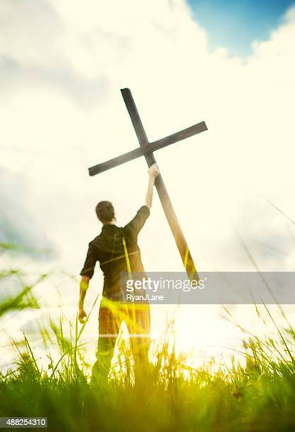 Man Holding Up Cross of Christ
