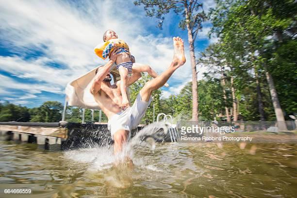 Man holding up daughter jumping from slide at Jackson Lake, Georgia, USA