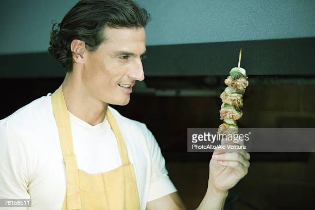 Man holding up grilled kebab