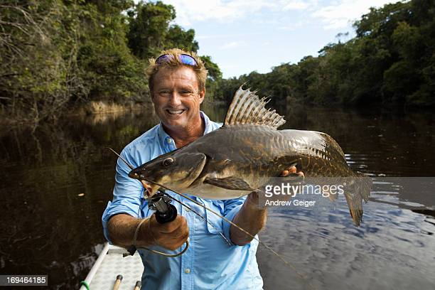 man holding up large surubim catfish on amazon. - big fish stock pictures, royalty-free photos & images
