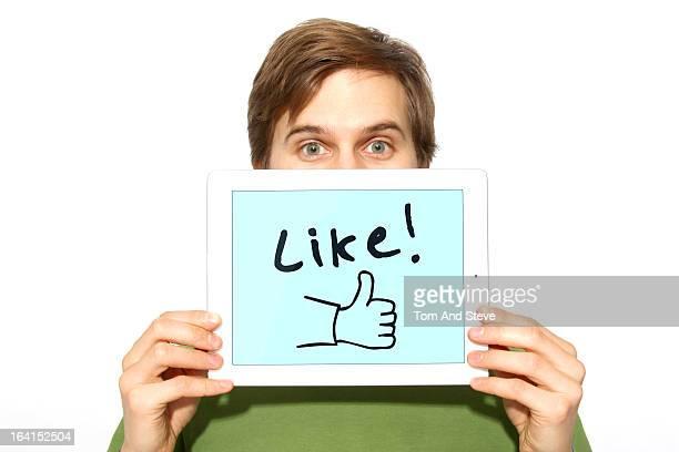 Man holding up like symbol on tablet computer