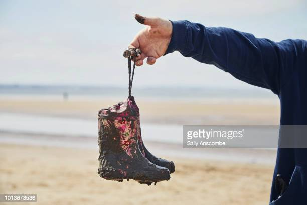 Man holding up muddy wellington boots