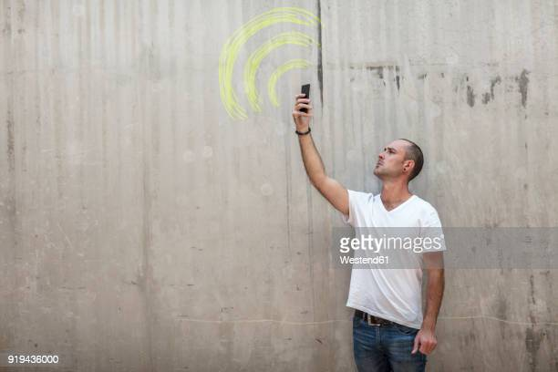 Man holding up phone looking for signal with wifi sign drawn in yellow chalk on concrete wall