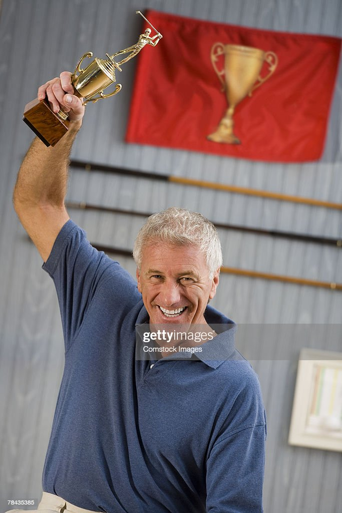 Man holding up trophy in victory : Stockfoto