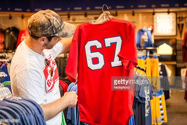 man holding up t-shirt in store - heshphoto stock pictures, royalty-free photos & images