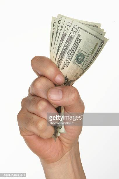 Man holding US currency (focus on bills)