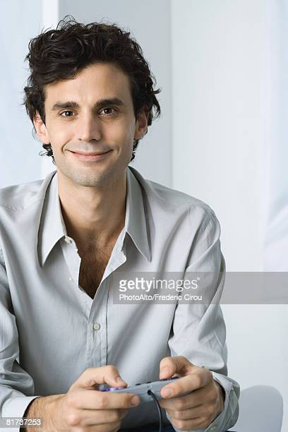 Man holding video game controller, smiling at camera