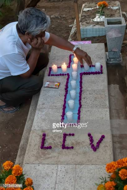Veillée de Holding homme près tombe de sa grand-mère sur le Día de los Muertos, Oaxaca