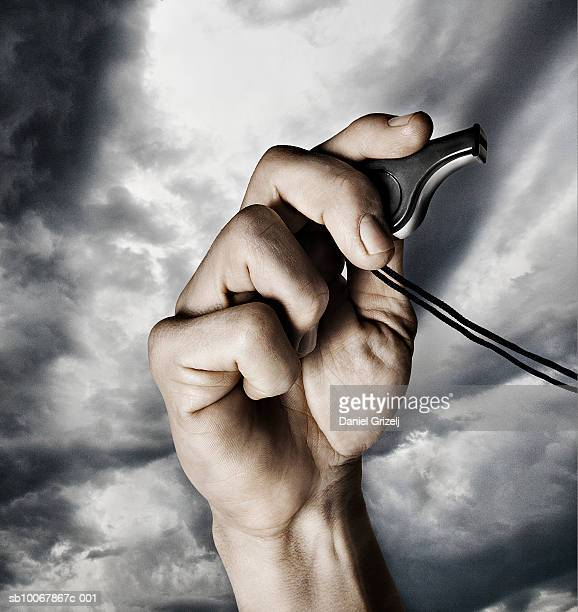 man holding whistle, close-up of hand - 笛 ストックフォトと画像