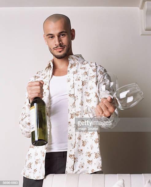 Homem segurando a garrafa de vinho e copos