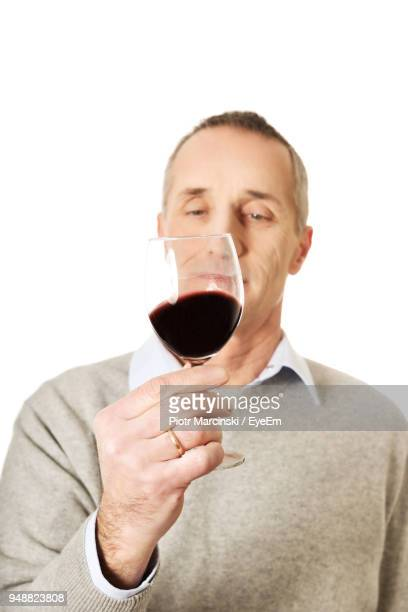 Man Holding Wineglass Against White Background