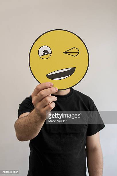 Man holding winking emoticon face in front of his face