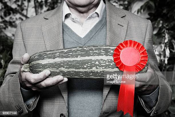 man holding winning marrow - black and white vegetables stock photos and pictures