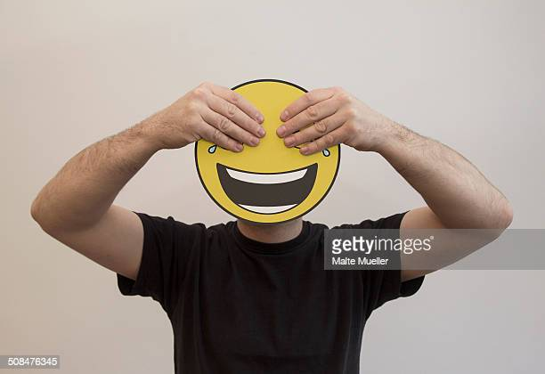 man holding with hands covering the eyes of a happy emoticon face - smiley face stock pictures, royalty-free photos & images