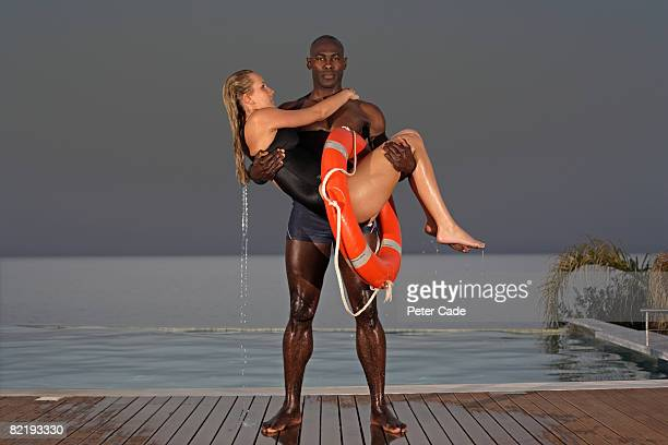 man holding woman after saving her from pool - barefoot black men stock pictures, royalty-free photos & images