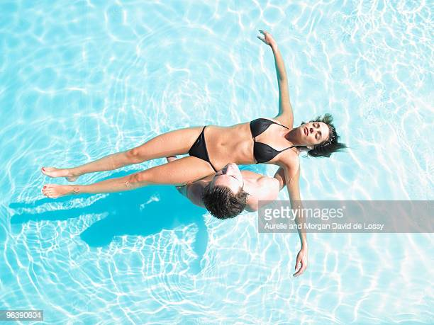 man holding woman floating in pool - swimwear stock pictures, royalty-free photos & images