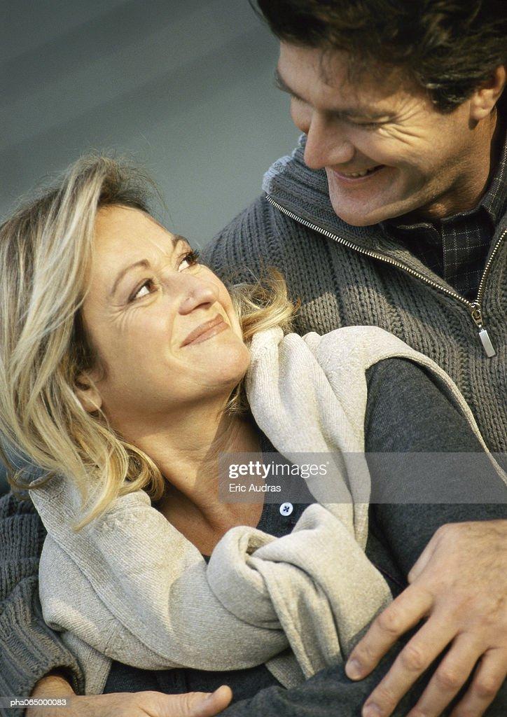 Man holding woman from behind, woman looking back at man, close up. : Stockfoto