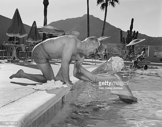 man holding woman's hand at swimming pool, smiling - 1965 stock pictures, royalty-free photos & images