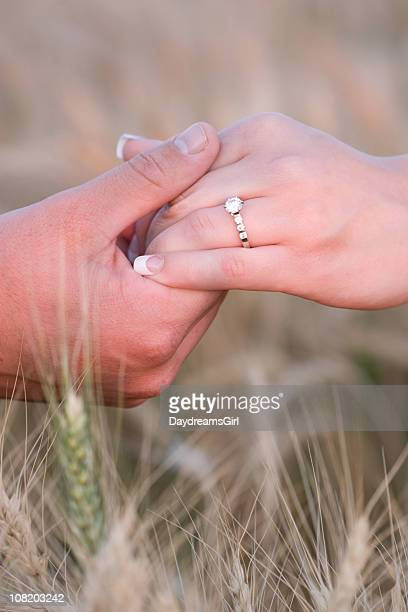 Man Holding Woman's Hand with Diamond Engagement Ring in Field