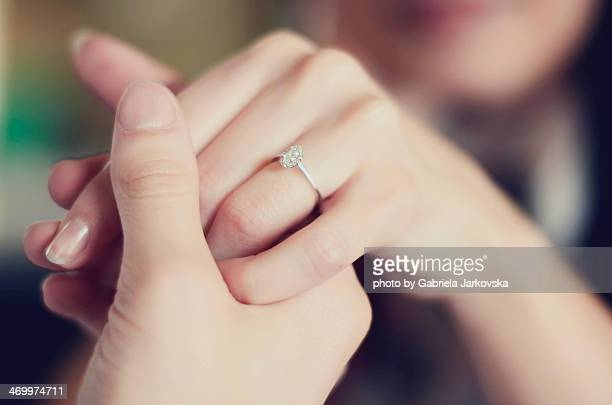 Man holding womans hand with engagement ring