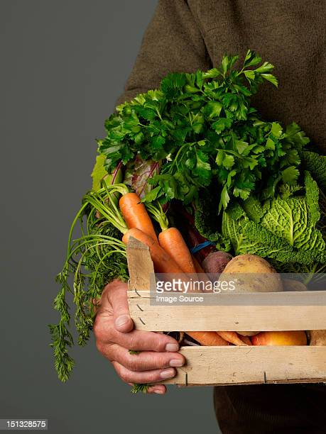 Man holding wooden crate of vegetables