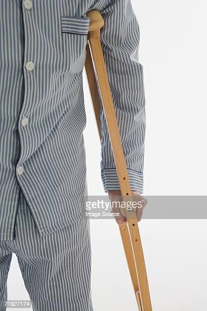 Man holding wooden crutch