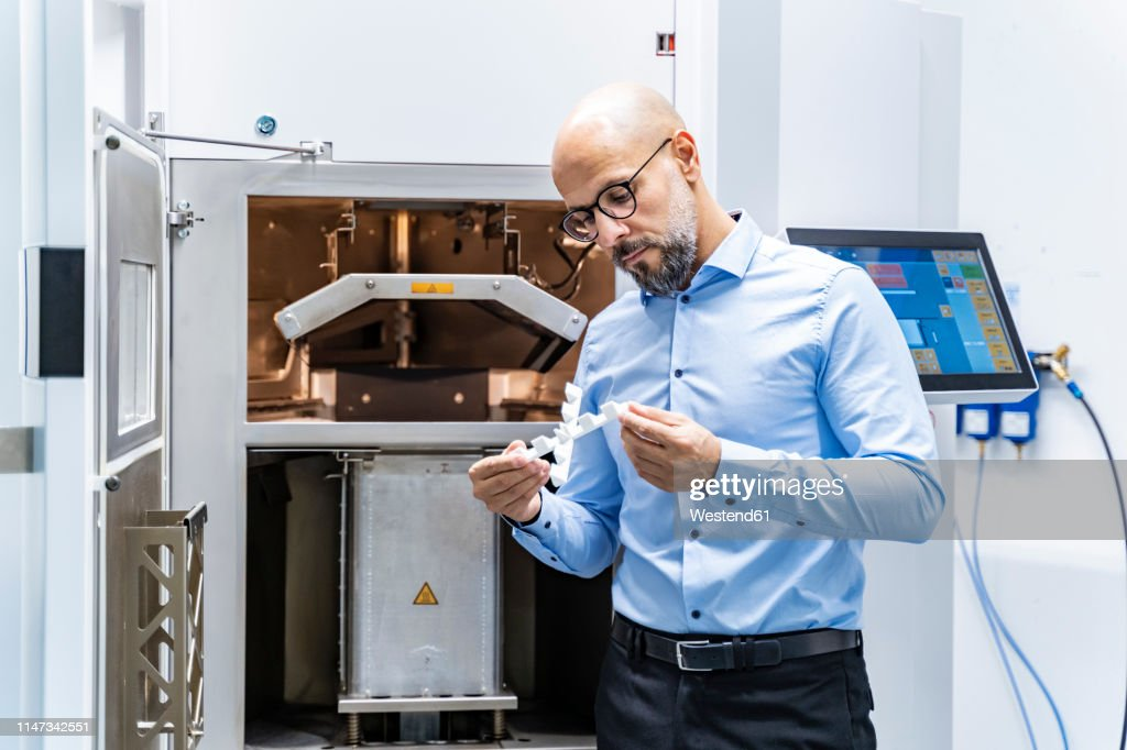 Man holding workpiece at 3d printer : Stock-Foto