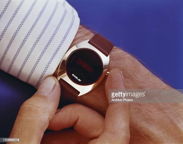 Man holding wrist watch, close-up