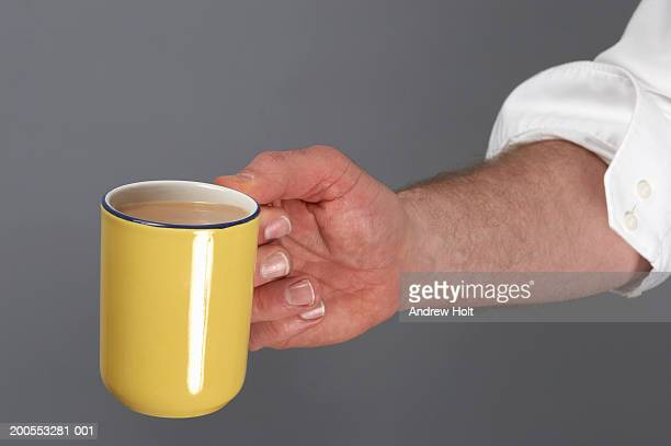 Man holding yellow cup of tea with milk, close-up of hand