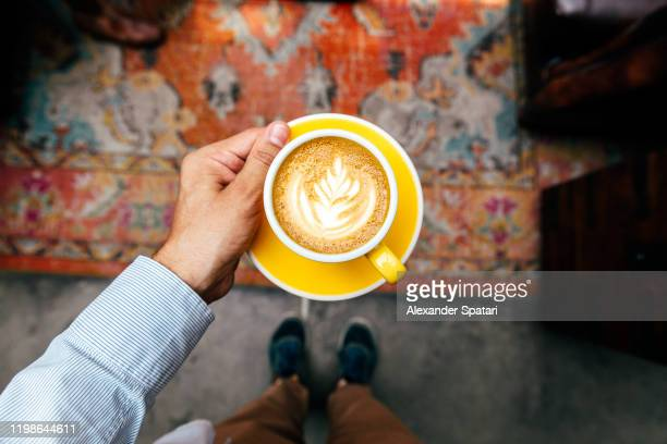 man holding yellow cup with cappuccino, personal perspective view - coffee stock pictures, royalty-free photos & images
