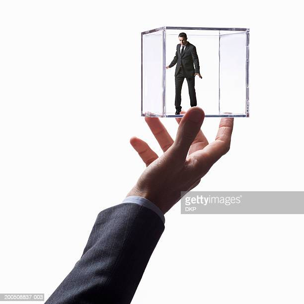 Man holding young businessman in transparent box (Digital Composite)