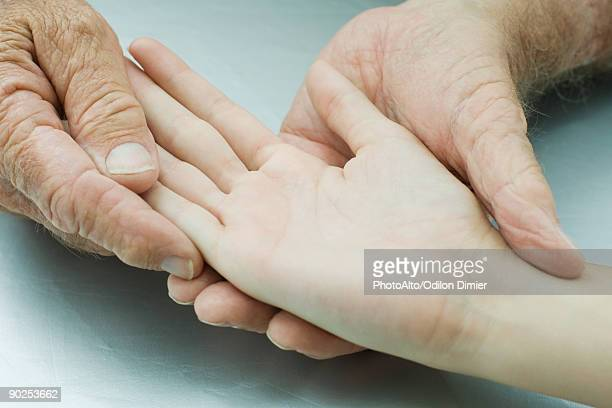 Man holding young person's hand, palm facing up, cropped view