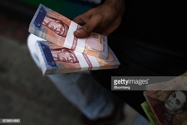 A man holds 10Bolivar notes for a photograph after exchanging his 100Bolivar notes at a bank in Caracas Venezuela on Wednesday Dec 14 2016 Roughly 24...