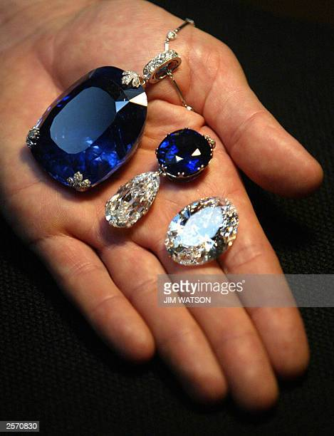 A man holds a 478 carat sapphire which was previously owned by Queen Marie of Romania Belle Epoque necklace with cushionshaped sapphire weighing 4764...