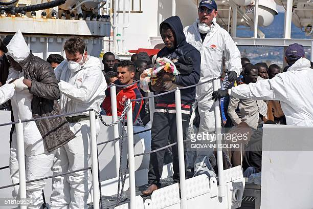 A man holds a baby as migrants and refugees arrive in the port of Messina following a rescue operation at sea by the Italian Coast Guard ship...