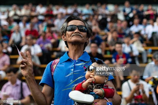 A man holds a baby doll during the season opening horse race at the Sha Tin Racecourse of the Hong Kong Jockey Club in Hong Kong on September 2 2018