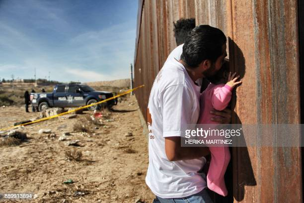 TOPSHOT A man holds a baby next the border wall between Mexico and United States during the 'Keep our dream alive' event in Ciudad Juarez Chihuahua...