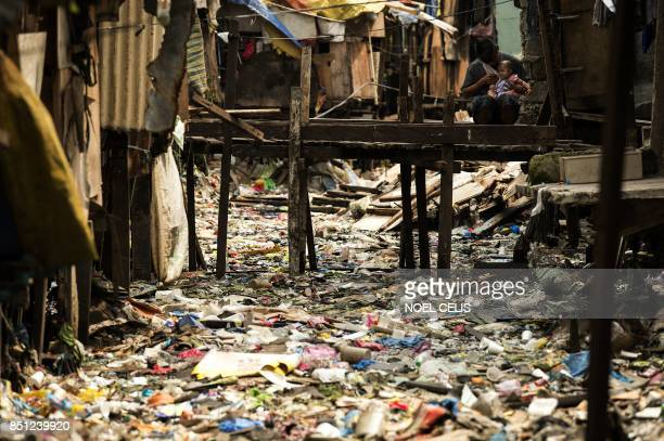 A man holds a baby on a bridge over a garbage filled creek in Manila on September 22 2017 Giant Western consumer products brands led by Nestle...
