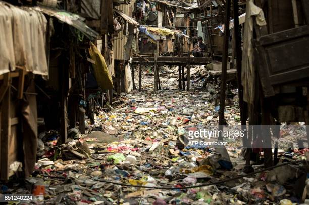 TOPSHOT A man holds a baby on a bridge over a garbage filled creek in Manila on September 22 2017 Giant Western consumer products brands led by...