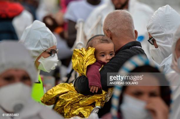 TOPSHOT A man holds a baby with a rescue blanket in his arms as a member of the Italian red cross examines them after they disembarked from the Topaz...